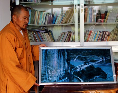 Monk showing picture of the old Jihong Bridge.